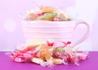 Tasty candies in mug on table on bright background