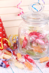 Tasty candies in jar on table close up