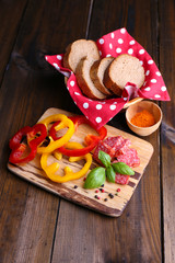Composition with knife,  tasty salami sausage, sliced bread and