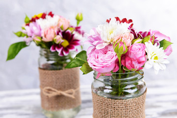 Beautiful bouquet of bright flowers in jars