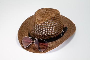 Summer straw hat with sunglases isolated on white