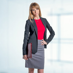 Portrait of young business woman with red folder gray skirt