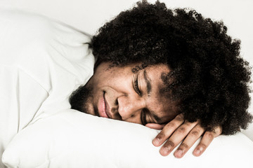 Young man sleeping on white pillow