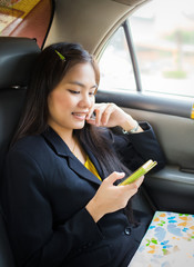 Beautiful young Asian businesswomen using a smart phone on car