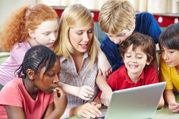 Schüler und Lehrer mit Computer im Internet