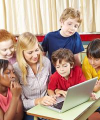 Schüler mit Lehrer am Laptop Computer