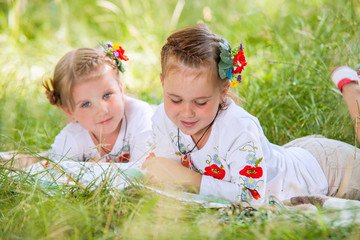 Two little girls reading books on the green meadow