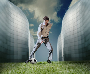 Man in casual suit playing in football near the modern buildings