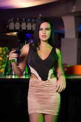Brunette woman holding cocktail in bar