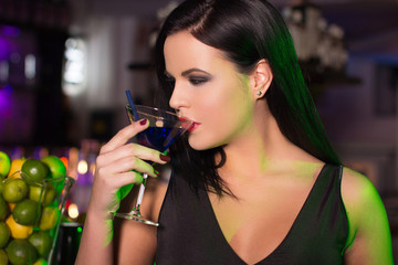 Woman drink cocktail in bar at night
