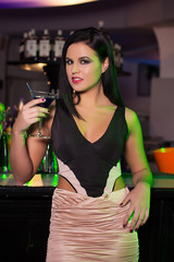 Woman holding cocktail in bar