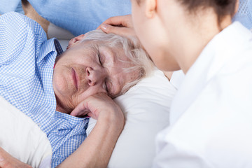 A nurse assists older woman