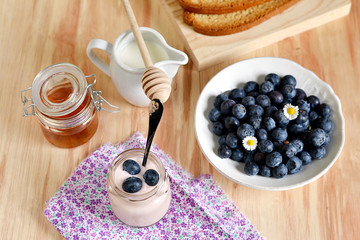 Breakfast with blueberries, honey and yogurt