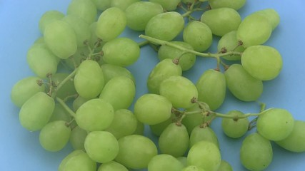 Ripe green grapes rotating a blue  background.