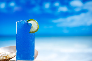 blue slush ice in glass  on sea beach background