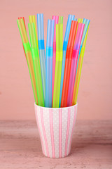 Straws in cup on pink background