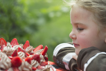 Small girl looks at a strawberry cake