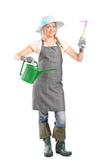 Female gardener holding mattock and watering can