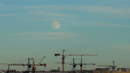 The moon moves in the sky over a building site