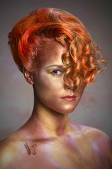Woman with striking makeup and extravagant hairstyle in studio.