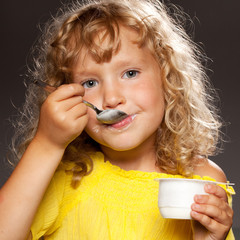 Little girl eating yogurt