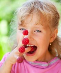 Little girl with raspberry