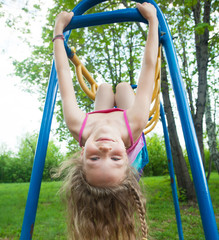 Girl hanging on horizontal bar