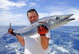 Pêche au gros, pêcheur tenant un wahoo pris à la traine