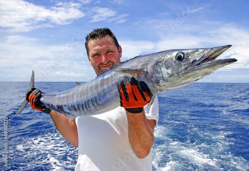 Deurstickers Vissen Pêche au gros, pêcheur tenant un wahoo pris à la traine