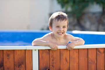 Cute kid in a big swimming pool, smiling