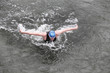 swimmer in wetsuit performing the butterfly stroke in ocean