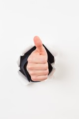 Thumbs up bursting through paper