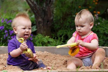 two grubby kids playing in the sandbox