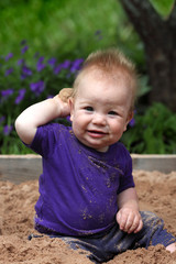 grubby little boy playing in a sandbox