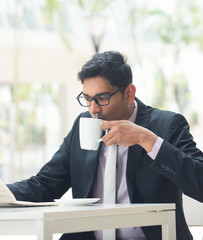 indian business male with newspaper and coffee at a cafe