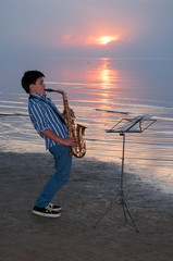 Boy with alto sax on the beach