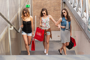 Three beautiful woman walks up the stairs, they go shopping