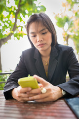 Beautiful Asian business woman using mobile for communication