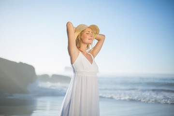 Smiling blonde standing at the beach in white sundress and sunha