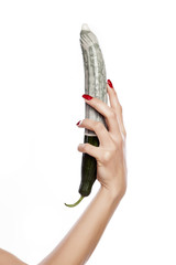 woman's hand holding a cucumber with a condom
