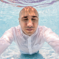 Underwater portrait of bald man with closed eyes wearing white s