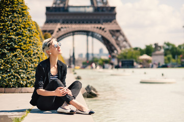 Fashion young blonde woman portrait in front of the Eiffel Tower