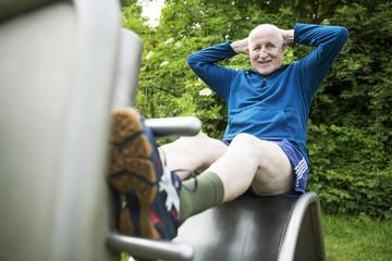 sportlicher senior trainiert an Fitnessgeräten im Park