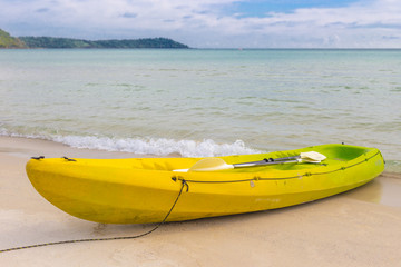 Yellow kayak on the sand beach