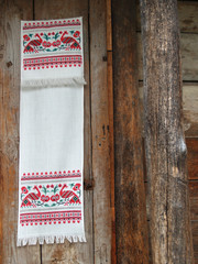 The Ukrainian towel hangs on a wall of the old wooden house