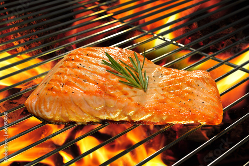 Grilled salmon on the flaming grill.