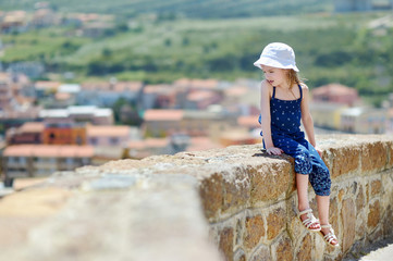 Little girl sitting on a wall enjoying a view