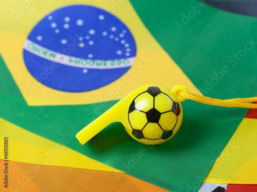 football shape whistle on brazil flag background.