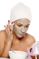 young beautiful woman applied a mask on his face