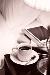 a cup of coffee on the bedside table and lamp